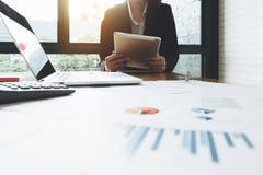 Mujer de negocios que se sienta en la oficina y que usa COM de la tableta y del ordenador portátil fotos de archivo