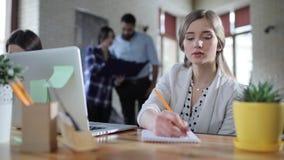 Mujer de negocios que se sienta en oficina con el ordenador portátil, escribiendo nuevas ideas en su cuaderno y tipo en el ordena metrajes