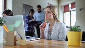 Mujer de negocios que se sienta en oficina con el ordenador portátil y que piensa en concepto de lanzamiento Otros trabajadores p metrajes