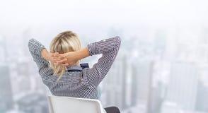 Mujer de negocios que se sienta en silla con el horizonte de la ciudad en fondo imagen de archivo