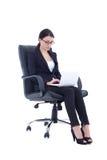 Mujer de negocios que se sienta en silla y que trabaja con el ordenador portátil aislado Fotos de archivo libres de regalías
