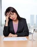 Mujer de negocios que se sienta en su escritorio Imagen de archivo