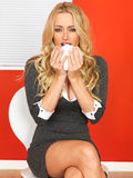 Mujer de negocios que se sienta en una silla con el estornudo frío Foto de archivo libre de regalías