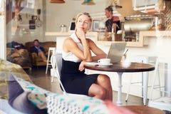 Mujer de negocios que se sienta en una tabla en pequeña cafetería foto de archivo