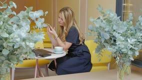 Mujer de negocios que se sienta en una tabla en un café de consumición del café y las aplicaciones en un smartphone metrajes