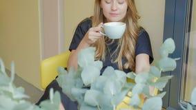 Mujer de negocios que se sienta en una tabla en un café de consumición del café y las aplicaciones en un smartphone almacen de metraje de vídeo