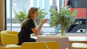 Mujer de negocios que se sienta en una tabla en un café de consumición del café y que trabaja en un ordenador portátil almacen de video