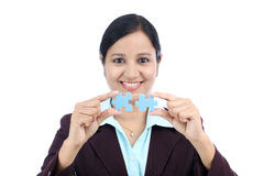Mujer de negocios que se une a dos pedazos del rompecabezas Imagen de archivo