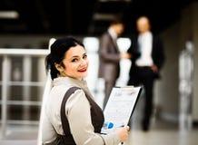 Mujer de negocios que sonríe, en un ambiente de la oficina Imagen de archivo