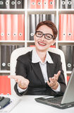Mujer de negocios que sonríe y que gesticula la recepción Imagenes de archivo