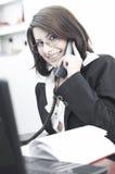 Mujer de negocios que sonríe y que habla en el teléfono Fotos de archivo