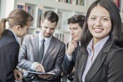 Mujer de negocios que sonríe y que mira la cámara con sus colegas que hablan y que miran abajo una tableta digital en el backgroun Imágenes de archivo libres de regalías