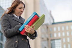Mujer de negocios que sostiene carpetas con los documentos al aire libre Foto de archivo libre de regalías