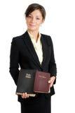 Mujer de negocios que sostiene dos biblias Fotos de archivo
