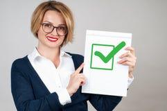 Mujer de negocios que sostiene el papel en blanco con el control Foto de archivo libre de regalías