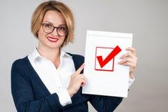 Mujer de negocios que sostiene el papel en blanco con el control Imagen de archivo