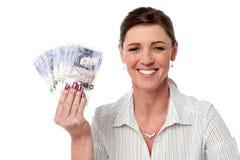 Mujer de negocios que sostiene la fan de las notas de la moneda Fotos de archivo