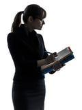 Mujer de negocios que sostiene los ficheros de las carpetas que escriben la silueta Imagen de archivo
