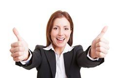 Mujer de negocios que sostiene pulgares Foto de archivo libre de regalías