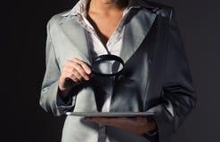 Mujer de negocios que sostiene una lupa Foto de archivo libre de regalías