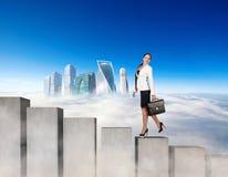 Mujer de negocios que sube los bloques concretos de las escaleras imagen de archivo