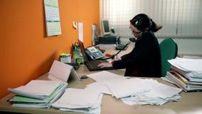 Mujer de negocios que tiene mucho trabajo en la oficina, haciendo llamada de teléfono