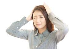 Mujer de negocios que tiene un dolor de cabeza Fotos de archivo
