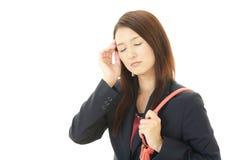 Mujer de negocios que tiene un dolor de cabeza Imagenes de archivo