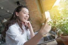 Mujer de negocios que toma el selfie en el mphone elegante en tiempo del descanso para tomar caf? en su lugar de trabajo concepto foto de archivo libre de regalías