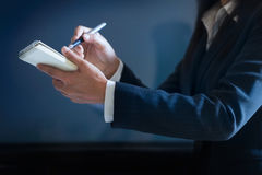 Mujer de negocios que toma notas en documento sobre fondo azul marino imágenes de archivo libres de regalías