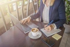 Mujer de negocios que toma notas y que usa el ordenador portátil interior fotos de archivo libres de regalías