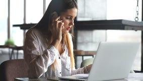Mujer de negocios que trabaja con el ordenador portátil y que habla en el teléfono celular metrajes