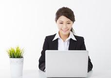 Mujer de negocios que trabaja con el ordenador portátil y la planta verde Imagenes de archivo
