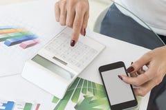 Mujer de negocios que trabaja con la calculadora financiera del documento Imagenes de archivo