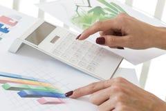 Mujer de negocios que trabaja con la calculadora financiera del documento Fotos de archivo libres de regalías