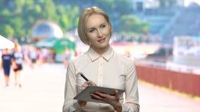 Mujer de negocios que trabaja con una pluma en una tableta almacen de video
