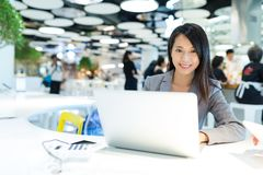 Mujer de negocios que trabaja en el ordenador portátil en lugar de co-trabajo foto de archivo