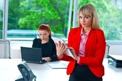 Mujer de negocios que trabaja en la tableta con el colega en fondo Imágenes de archivo libres de regalías