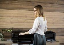 Mujer de negocios que trabaja en oficina por la impresora Fotografía de archivo