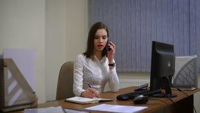 Mujer de negocios que trabaja en su ordenador y que habla en el teléfono almacen de metraje de vídeo