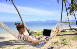 Mujer de negocios que trabaja en una hamaca en la playa fotos de archivo