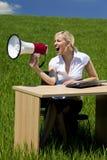 Mujer de negocios que usa el megáfono en un campo verde Imagenes de archivo