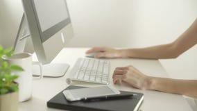 Mujer de negocios que usa el ordenador con el ratón inalámbrico para Internet que practica surf en oficina almacen de metraje de vídeo
