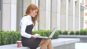 Mujer de negocios que usa el ordenador portátil con una taza de café en la terraza almacen de metraje de vídeo