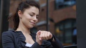 Mujer de negocios que usa el smartwatch para hojear almacen de metraje de vídeo