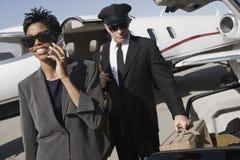Mujer de negocios que usa el teléfono móvil en el campo de aviación imagen de archivo