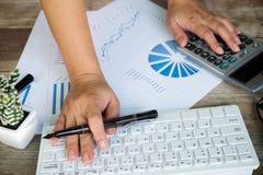 Mujer de negocios que usa la calculadora del ordenador para calcular el número Imagen de archivo