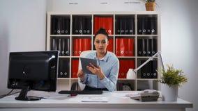 Mujer de negocios que usa la tablilla almacen de metraje de vídeo