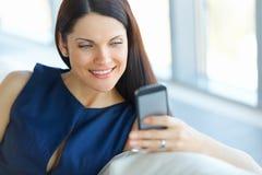Mujer de negocios que usa su Smartphone en la oficina Foto de archivo