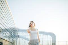 Mujer de negocios que usa un teléfono y un reloj mientras que se coloca en al aire libre foto de archivo libre de regalías